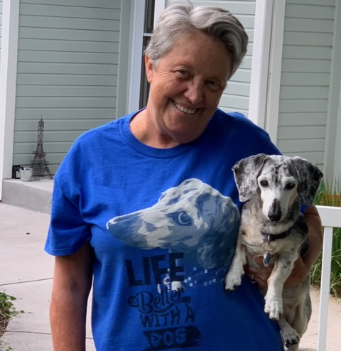Picture of Toni Theisen holding dog with shirt with dog picture