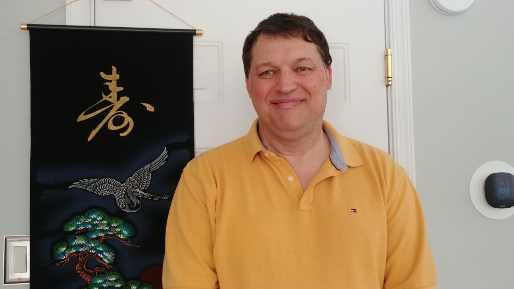 Image of Greg Nedved in yellow shirt, standing with black Chinese scroll behind