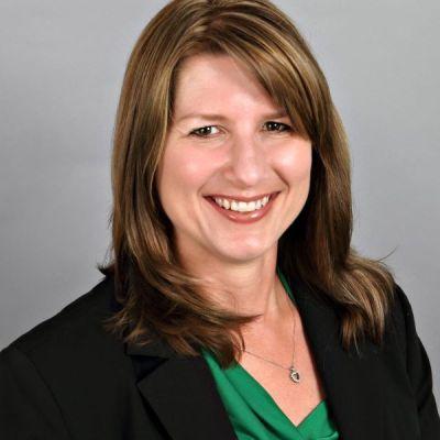 Picture of Linda Zins-Adams, wearing green shirt and black blazer. Long brown hair.