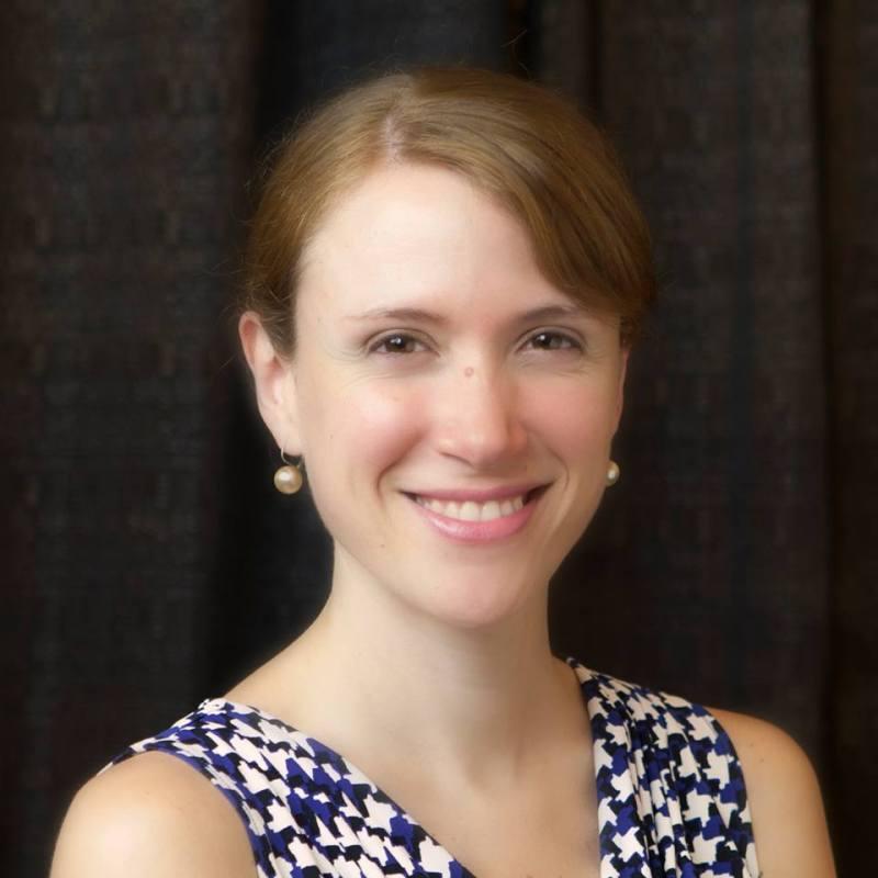 Dark background. Woman smiling at camera, reddish brown hair, earrings. Shirt is blue, white, black pattern.